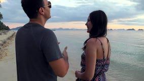 Junge Paare, die auf dem Strand sprechen stock video footage