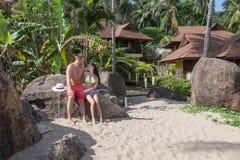 Junge Paare, die auf dem Strand vor dem hintergrund der Bungalows sitzen Stockfoto