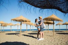 Junge Paare, die auf dem streichelnden Strand stehen stockfotografie