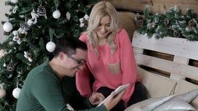 Junge Paare, die auf dem Stuhl sitzen und das Internet auf der Tablette grasen stock video footage