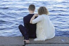 Junge Paare, die auf dem Ufergegendrecht durch das Wasser sitzen Stockfotos