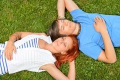 Junge Paare, die auf den Grasaugen geschlossen liegen Lizenzfreie Stockfotos