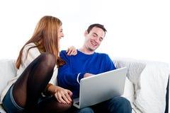 Junge Paare, die auf der Couch mit Laptop sich entspannen Stockfotos