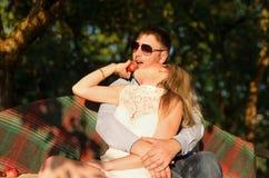 Junge Paare, die auf der Gartenbank sitzen Stockbilder
