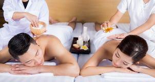 Junge Paare, die auf der Massagetabelle und -c$lächeln liegen Stockfotografie