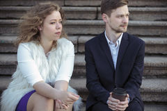 Junge Paare, die auf der Treppe vor dem Haus sitzen Stockfotografie