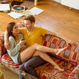 Junge Paare, die auf die Couch streicheln Stockbild