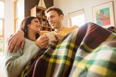Junge Paare, die auf die Couch unter Decke streicheln Stockfoto