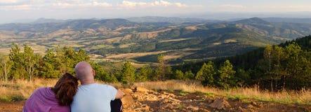 Junge Paare, die auf die Oberseite des Berges am sonnigen Sommertag sitzen Stockfotografie