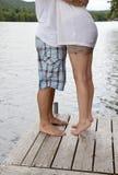 Junge Paare, die auf Dock umarmen Lizenzfreies Stockfoto