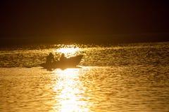 Junge Paare, die auf ein Boot schwimmen Stockfoto