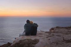 Junge Paare, die auf eine Klippe bei Sonnenuntergang streicheln lizenzfreies stockfoto