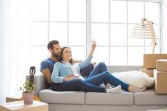 Junge Paare, die auf eine neue Verlegung der Wohnung zusammenrücken Lizenzfreies Stockbild