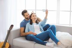 Junge Paare, die auf eine neue Verlegung der Wohnung zusammenrücken Lizenzfreie Stockfotos
