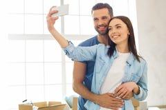 Junge Paare, die auf eine neue Verlegung der Wohnung zusammenrücken Lizenzfreie Stockbilder
