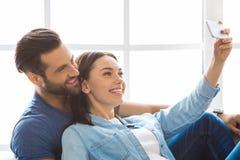 Junge Paare, die auf eine neue Verlegung der Wohnung zusammenrücken Stockbilder