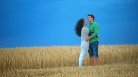 Junge Paare, die auf einem Gebiet küssen Junge Frau, die einen kaukasischen Mann mitten in einem Weizenfeld umarmt und jedes küss stock video