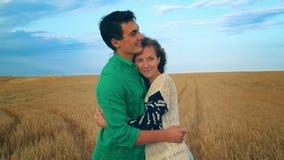 Junge Paare, die auf einem Gebiet küssen Junge Frau, die einen kaukasischen Mann mitten in einem Weizenfeld umarmt und jedes küss stock video footage