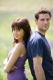 Junge Paare, die auf einem Gebiet stehen Stockbild