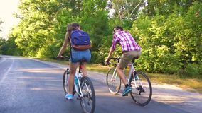 Junge Paare, die auf einen Waldweg an einem sammer Tag radfahren stock footage