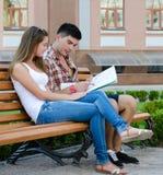 Junge Paare, die auf einer Bank liest eine Karte sitzen stockfotos