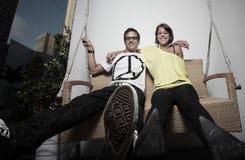 Junge Paare, die auf einer Bank schwingen Stockfotografie