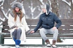 Junge Paare, die auf einer Bank sitzen lizenzfreies stockfoto