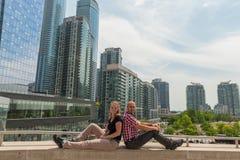 Junge Paare, die auf einer Brücke in Toronto sitzen Lizenzfreies Stockfoto