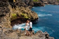 Junge Paare, die auf einer Klippe durch das Meer küssen stockfotografie