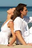 Junge Paare, die auf einer Seeküste sitzen Lizenzfreie Stockfotografie