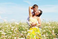 Junge Paare, die auf Feld der Blumen spielen Stockfotografie