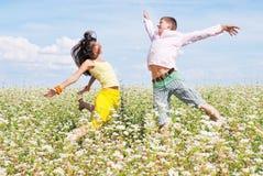 Junge Paare, die auf Feld der Blumen spielen Lizenzfreie Stockbilder