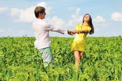 Junge Paare, die auf Feld am sonnigen Tag spielen Stockfoto