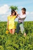 Junge Paare, die auf Feld am sonnigen Tag spielen Lizenzfreie Stockfotos