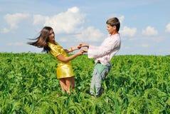 Junge Paare, die auf grünem Feld spielen Lizenzfreies Stockfoto