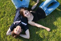 Junge Paare, die auf Gras liegen lizenzfreies stockbild