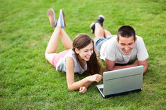 Junge Paare, die auf Gras mit Laptop liegen Stockbild