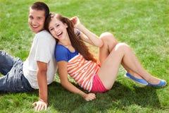 Junge Paare, die auf Gras sitzen Stockbilder