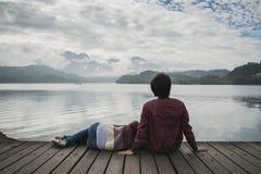 Junge Paare, die auf hölzernem Pier sitzen und Ansicht der Natur schauen stockfotos