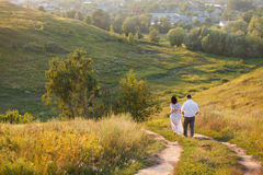 Junge Paare, die auf Hügel gehen stockbilder
