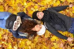 Junge Paare, die auf Herbstblättern sich entspannen Stockfotos