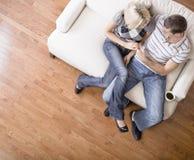 Junge Paare, die auf Liebes-Sitz sitzen Lizenzfreie Stockfotos