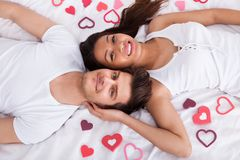 Junge Paare, die auf Matratze liegen Stockfoto
