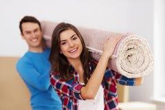 Paare, die einen Teppich halten Stockfoto
