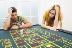 Junge Paare, die auf Roulettetisch verlieren lizenzfreie stockfotografie