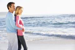 Junge Paare, die auf Sandy Beach Looking Out To-Meer stehen Stockfotos