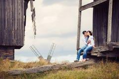 Junge Paare, die auf Schritten der alten Windmühle küssen Lizenzfreie Stockfotografie