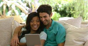 Junge Paare, die auf Sofa sitzen und digitale Tablette im Wohnzimmer verwenden stock video footage