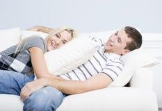 Junge Paare, die auf Sofa stützen Lizenzfreie Stockfotografie