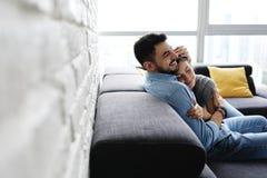 Junge Paare, die auf Sofa umarmen und küssen stockfoto